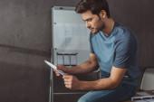 Boční pohled na návrháře ux držícího náčrty při sezení u stolu v kanceláři