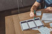 Oříznutý pohled na designéra, který vyvíjí rozvržení mobilních webových stránek u stolu