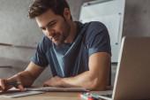 Selektivní zaměření smajlíka návrháře plánování mobilní aplikace s náčrtky a notebook na stole