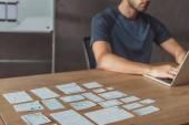 Oříznutý pohled vývojáře uxu pomocí notebooku vedle návrhářských skic na stole, selektivní zaměření