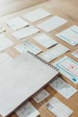 Vysokoúhlý pohled na notebook a uživatelské zkušenosti design náčrty na dřevěném stole