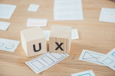 Selective focus of wooden cubes with ux letter and layouts on table stock vector