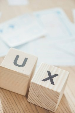 Selective focus of letters ux on wooden cubes on table stock vector