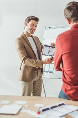 Selective focus of smiling designer showing screens of mobile responsive website development to colleague in office stock vector