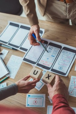 Cropped view of designers holding cubes with ux letters while working with layouts at table stock vector