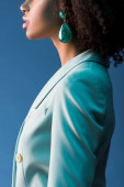 cropped view of african american woman in suit and earring isolated on blue
