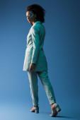 Afrikanische Amerikanerin im Anzug blickt in die Kamera auf blauem Hintergrund