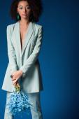 atraktivní africká americká žena drží kytice izolované na modré