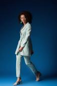 atraktivní africký americký žena chůze na modrém pozadí