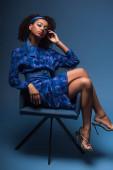 attraktive afrikanisch-amerikanische Frau mit geschlossenen Augen sitzt auf einem Sessel auf blauem Hintergrund