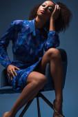 attraktive afrikanisch-amerikanische Frau sitzt auf Sessel isoliert auf blau
