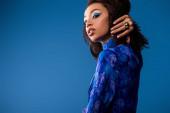 attraktive afrikanisch-amerikanische Frau in stilvollem Kleid schaut in die Kamera isoliert auf blau