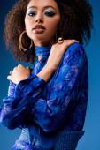 stylische afrikanisch-amerikanische Frau in Kleid mit Make-up, die in die Kamera schaut isoliert auf blau