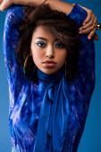 stylische afrikanisch-amerikanische Frau mit Make-up im Kleid schaut in die Kamera isoliert auf blau