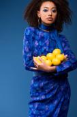 atraktivní africká americká žena drží citróny izolované na modré