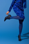 Photo cropped view of african american woman in dress touching her footwear on blue background