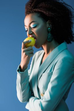 Stylish african american woman with makeup eating lemon isolated on blue stock vector