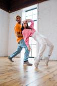 attraktive Mädchen Breakdance mit glücklichen afrikanisch-amerikanischen Mann mit Hut