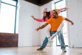 veselý africký Američan muž piggybacking atraktivní tanečnice