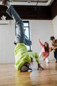 Selektiver Fokus des afrikanisch-amerikanischen Mannes in Mütze Breakdance in der Nähe emotionaler Tänzer