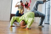 szelektív fókusz afro-amerikai férfi breakdancing közelében érzelmi táncosok