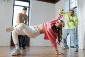selective focus of stylish girl breakdancing near emotional multicultural men