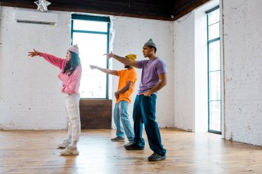 side view of attractive girl gesturing while breakdancing with handsome multicultural men in hats