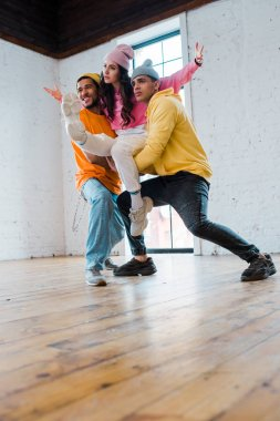 stylish multicultural men in hats holding attractive dancer