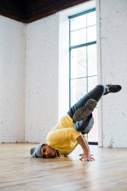 Stylish man in hat breakdancing in dance studio stock vector