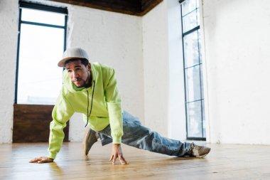 Handsome african american man in cap breakdancing in dance studio stock vector