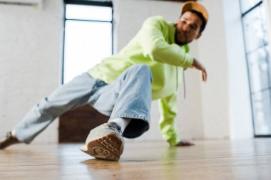 Selective focus of stylish african american man in cap breakdancing in dance studio stock vector