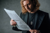 napjatý módní obchodník v černém obleku drží noviny v tmě