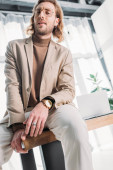 Photo low angle view of confident fashionable businessman sitting on desk and posing in office