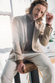 Photo low angle view of elegant fashionable businessman sitting on desk and looking at camera in office