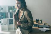 elegantní módní obchodník s rukama na bundě dívá pryč na slunci v kanceláři