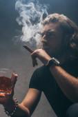 Fotografie angespannter modischer Geschäftsmann im schwarzen Outfit, Zigarre rauchend und Whiskey trinkend nahe grauer Wand