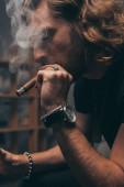 Fotografie modischer Geschäftsmann im schwarzen Outfit, Zigarre rauchend