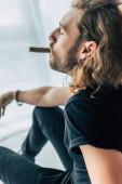 divatos alkalmi üzletember teljes fekete ruhában dohányzik szivar csukott szemmel az irodában