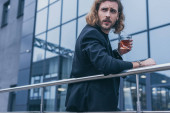 Photo fashionable businessman in black suit holding glass of whiskey near office building and railing