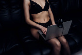 Cropped view of seductive woman in black underwear using laptop with web camera on couch