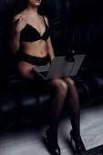 Oříznutý pohled na sexy ženu ve spodním prádle vzlétnout podprsenka při použití webové kamery na gauči