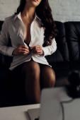 Selektivní zaměření sexy dívka svlékání tričko před notebookem s webovou kamerou