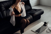 Cropped view of sexy girl taking off shirt while posing at web camera on couch