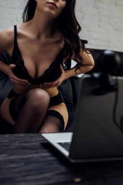 Cropped view of beautiful girl in bra showing breast while posing at laptop with web camera