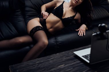 Cropped view of sexy webcam model posing on couch by laptop stock vector