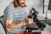 oříznutý pohled na šťastný editor držící digitální fotoaparát