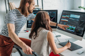 bärtige Kunstredakteurin zeigt mit dem Finger auf Computermonitor neben Frau