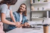 selektivní zaměření šťastného animátora při pohledu na spolupracovníka
