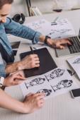 oříznutý pohled animátora ukazujícího prstem na kreslený náčrt poblíž spolupracovníka