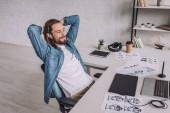 veselý ilustrátor se usmívá blízko gadgets a skici